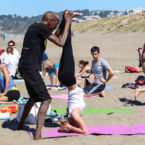 Yoga teacher adjust yoga student