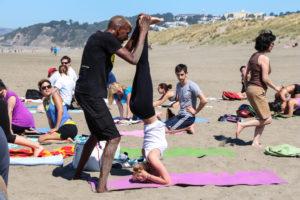 Yoga teacher adjust yoga student